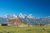 An old barn at Mormon Row is lit by the morning sun with the Teton Range rising in the distance. Mormon Row, Grand Teton National Park, Wyoming, USA. Image #12998