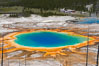 Grand Prismatic Spring (left) and Excelsior Geyser (right).  Grand Prismatic Spring displays a stunning rainbow of colors created by species of thermophilac (heat-loving) bacteria that thrive in narrow temperature ranges.  The blue water in the center is too hot to support any bacterial life, while the outer orange rings are the coolest water.  Grand Prismatic Spring is the largest spring in the United States and the third-largest in the world.  Midway Geyser Basin. Midway Geyser Basin, Yellowstone National Park, Wyoming, USA. Image #13571
