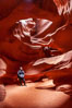 A hiker admiring the striated walls and dramatic light within Antelope Canyon, a deep narrow slot canyon formed by water and wind erosion. Navajo Tribal Lands, Page, Arizona, USA. Image #17995