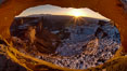 Mesa Arch spans 90 feet and stands at the edge of a mesa precipice thousands of feet above the Colorado River gorge. For a few moments at sunrise the underside of the arch glows dramatically red and orange. Island in the Sky, Canyonlands National Park, Utah, USA. Image #18085