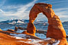 Delicate Arch, dusted with snow, at sunset, with the snow-covered La Sal mountains in the distance.  Delicate Arch stands 45 feet high, with a span of 33 feet, atop of bowl of slickrock sandstone. Delicate Arch, Arches National Park, Utah, Utah, USA. Image #18104