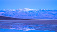 Sunrise lights Telescope Peak as it rises over the salt flats of Badwater, Death Valley.  At 11,049 feet, Telescope Peak is the highest peak in the Panamint Range as well as the highest point in Death Valley National Park.  At 282 feet below sea level, Badwater is the lowest point in North America. Badwater, Death Valley National Park, California, USA. Image #20549