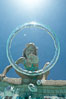 A bubble ring. A young girl reaches out to touch a bubble ring as it ascends through the water toward her. Image #20774