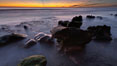 Sunset, sea cliffs, rocks and swirling water blurred in a long time exposure. Carlsbad, California, USA. Image #22198