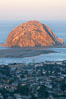 Morro Rock lit at sunrise, rises above Morro Bay which is still in early morning shadow. Morro Bay, California, USA. Image #22218