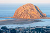 Morro Rock lit at sunrise, rises above Morro Bay which is still in early morning shadow. Morro Bay, California, USA. Image #22219