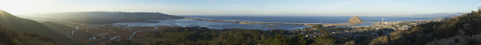 Morro Bay panorama, showing Morro Bay State Park (left), Morr Bay and barrier dunes, Pacific Ocean, and Morro Rock (right).  A composite of eight separate photographs. Morro Bay, California, USA. Image #22247