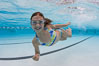 A young girl has fun swimming in a pool. Image #25291