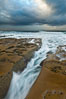 Waves wash over sandstone reef, clouds and sky. La Jolla, California, USA. Image #26338