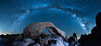 The Milky Way galaxy arcs above Arch Rock, panoramic photograph, cylindrical projection. Joshua Tree National Park, California, USA. Image #26848