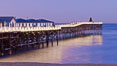 The Crystal Pier and Pacific Ocean at sunrise, dawn, waves blur as they crash upon the sand.  Crystal Pier, 872 feet long and built in 1925, extends out into the Pacific Ocean from the town of Pacific Beach. California, USA. Image #27239