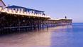 The Crystal Pier and Pacific Ocean at sunrise, dawn, waves blur as they crash upon the sand.  Crystal Pier, 872 feet long and built in 1925, extends out into the Pacific Ocean from the town of Pacific Beach. Pacific Beach, California, USA. Image #27240