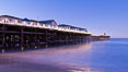 The Crystal Pier and Pacific Ocean at sunrise, dawn, waves blur as they crash upon the sand.  Crystal Pier, 872 feet long and built in 1925, extends out into the Pacific Ocean from the town of Pacific Beach. California, USA. Image #27241