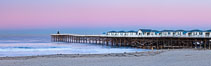 The Crystal Pier and Pacific Ocean at sunrise, dawn, waves blur as they crash upon the sand.  Crystal Pier, 872 feet long and built in 1925, extends out into the Pacific Ocean from the town of Pacific Beach. Pacific Beach, California, USA. Image #27244