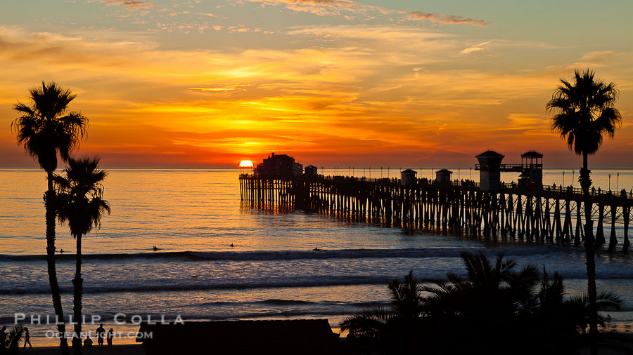 Oceanside Pier at sunset, clouds and palm trees with a brilliant sky at dusk