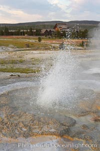 Anemone Geyser erupts, Old Faithful Inn visible in the distance.  Anemone Geyser cycles about every 7 minutes.  First the pools fills, then overflows, then bubbles and splashes before erupting.  The eruption empties the pools and the cycle begins anew.  Upper Geyser Basin, Yellowstone National Park, Wyoming
