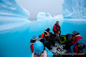 Visitors enjoy an inflatable ride through the strange environs of a bizarrely-shaped iceberg, on a cloudy day, Brown Bluff