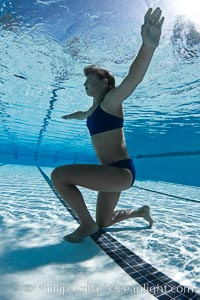 Athletic young girl underwater, performing isometric exercises