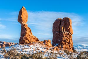 Balanced Rock, a narrow sandstone tower, appears poised to topple.  Sunset, winter, Arches National Park, Utah