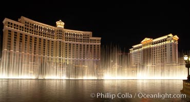 The Bellagio Hotel (left) and Caesar&#39;s Palace (right), seen behind the Bellagio fountains, at night.  The Bellagio Hotel fountains are one of the most popular attractions in Las Vegas, showing every half hour or so throughout the day, choreographed to famous Hollywood music