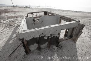Bombay Beach, lies alongside and below the flood level of the Salton Sea, so that it floods occasionally when the Salton Sea rises.  A part of Bombay Beach is composed of derelict old trailer homes, shacks and wharfs, slowly sinking in the mud and salt, Imperial County, California