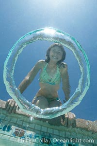 A bubble ring. A young girl watches as a bubble ring ascends through the water toward her
