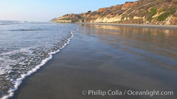 Ocean water washes over a flat sand beach, sandstone bluffs rise in the background, sunset, Carlsbad, California