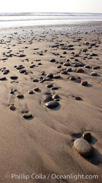 Cobblestones on a flat sand beach.  Cobble stones are polished round and smooth by years of wave energy.  They are alternately exposed and covered by sand depending on the tides, waves and seasons of the year.  Cobblestones are common on the beaches of southern California, contained in the sandstone bluffs along the beach and released onto the beach as the bluffs erode, Carlsbad