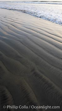 Patterns in the sand on a flat sandy beach at the water's edge, Carlsbad, California