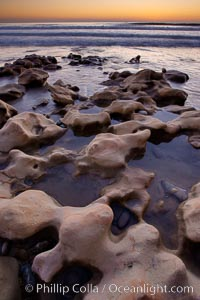 Rocks along the edge of the ocean at sunset, Carlsbad, California