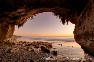 Sarah's Cavern, a natural sea cave hidden below sea cliffs in Carlsbad, opening onto a flat beach at sunset, inner walls adorned with graffiti