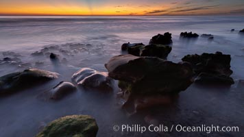 Sunset, sea cliffs, rocks and swirling water blurred in a long time exposure, Carlsbad, California