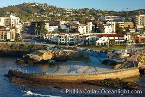 The Children's Pool in La Jolla, also known as Casa Cove, is a small pocket cove protected by a curving seawall, with the rocky coastline and cottages and homes of La Jolla seen behind it