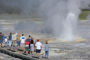 Visitors watch Clepsydra Geyser erupts almost continuously, reaching heights of  feet.  Its name is Greek for water clock, since at one time it erupted very regularly with a three minute interval.  Lower Geyser Basin, Yellowstone National Park, Wyoming