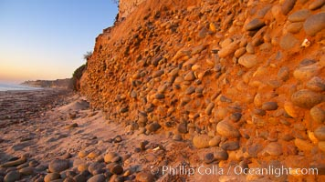 Cobblestones fall to the sand beach from the sandstone cliffs in which they are embedded, Carlsbad, California