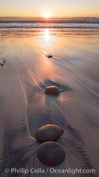 Cobblestone lies on the sand at the ocean&#39;s edge, sunset