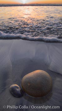 Cobblestone lies on the sand at the ocean's edge, sunset