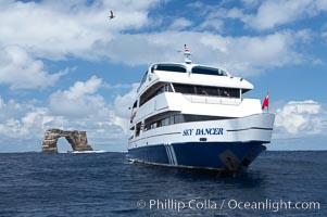 Sky Dancer, a liveaboard dive tour boat, at anchor near Darwin Island with Darwins Arch in the background