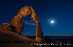 Delicate Arch and the Moon at Sunset.  The moon and clouds, with stars showing faintly in the sky, as sunset fades into night, Arches National Park, Utah