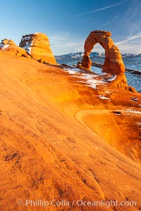 Delicate Arch, dusted with snow, at sunset, with the snow-covered La Sal mountains in the distance.  Delicate Arch stands 45 feet high, with a span of 33 feet, atop of bowl of slickrock sandstone. Delicate Arch, Arches National Park, Utah, USA, natural history stock photograph, photo id 18106