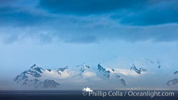 Distant icebergs, mountains, clouds, ocean at dawn, in the South Shetland Islands, near Deception Island