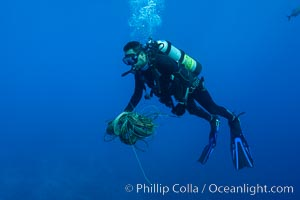 Diver collecting fishing line and debris from coral reef, Clipperton Island