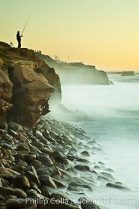 Fisherman at dawn along the La Jolla coastline, waves blur as they crash upon the Boomer Beach boulders