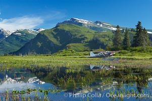 Float plane, water lilies and pond lie beneath the Chigmit Range near Silver Salmon Creek, Lake Clark National Park, Alaska