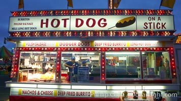 Food vendors at the Del Mar Fair, famous for their tasty, greasy, salty, fattening and generally unwholesome food, which visitors eat by the ton.  Bright lights at night. Del Mar Fair, Del Mar, California, USA, natural history stock photograph, photo id 20874