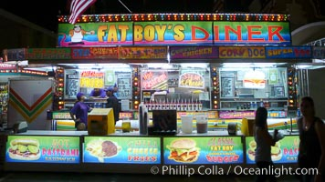 Food vendors at the Del Mar Fair, famous for their tasty, greasy, salty, fattening and generally unwholesome food, which visitors eat by the ton.  Bright lights at night. Del Mar Fair, Del Mar, California, USA, natural history stock photograph, photo id 20879