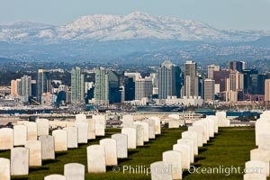 Tombstones at Fort Rosecrans National Cemetery, with downtown San Diego with snow-covered Mt. Laguna in the distance