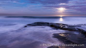 Breaking waves crash upon a rocky reef under the light of a full moon, La Jolla, California