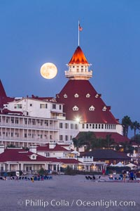 Full Moon Rising over Hotel del Coronado, known affectionately as the Hotel Del. It was once the largest hotel in the world, and is one of the few remaining wooden Victorian beach resorts. It sits on the beach on Coronado Island, seen here with downtown San Diego in the distance. It is widely considered to be one of Americas most beautiful and classic hotels. Built in 1888, it was designated a National Historic Landmark in 1977