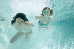 Two girls swimming through a cloud of bubbles in a swimming pool